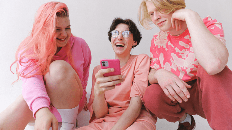 three women wearing pink with pink hair holding phone and laughing