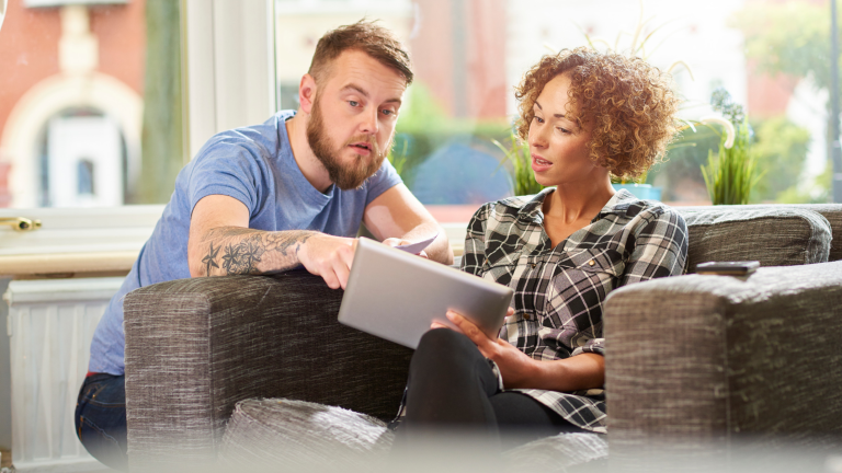 man and woman sitting at home looking at tablet